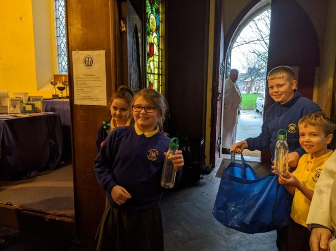 Canon Burrows pupils giving out reusable bottles to members of their community.