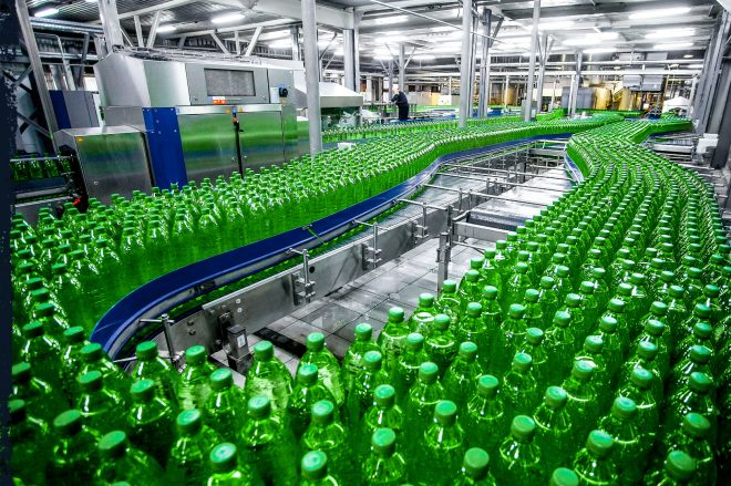 A production line of green plastic bottles