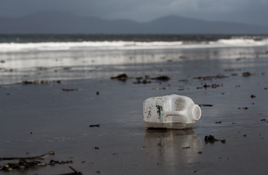 Old plastic milk bottle on beach